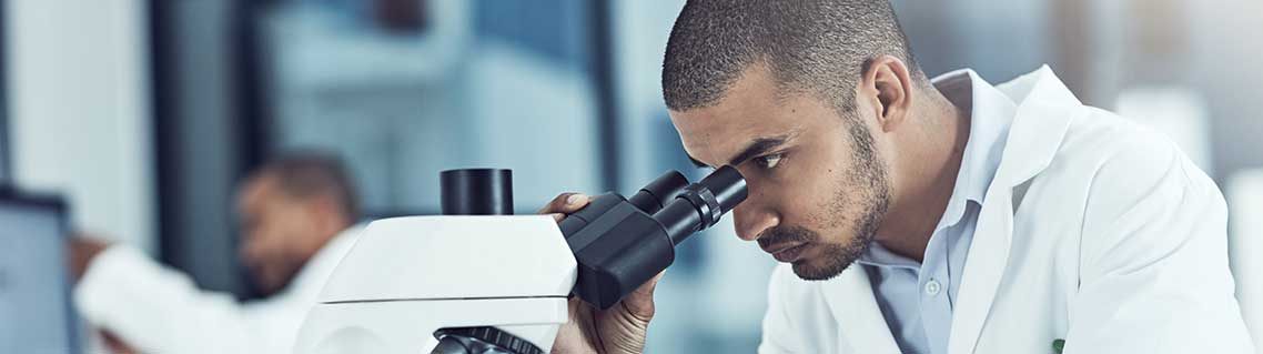 Man uses a microscope in a laboratory
