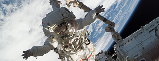 NASA astronaut Rick Linnehan, secured to the end of Canadarm2