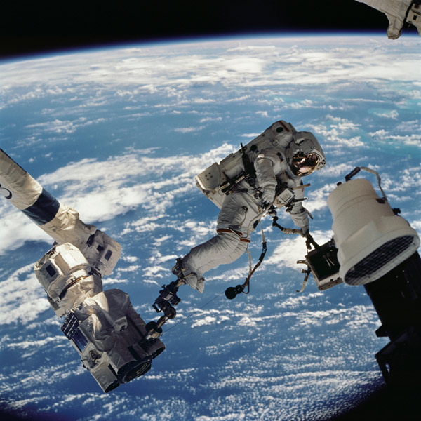 American astronaut David Wolf wears the EVARM dosimeter for a spacewalk on October 10, 2002. He is being moved by Canadarm. (Photo: NASA)