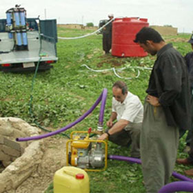 Volunteers help install and test a water purification system