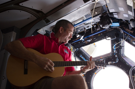 Strumming on a guitar in the Cupola module.