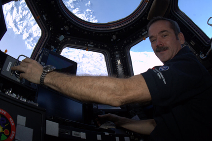 Hadfield in the cupola at the helm of the Canadarm2