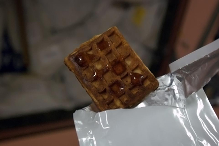 A photo of a weightless waffle with maple syrup