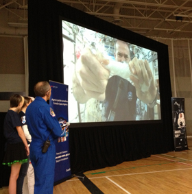 Hadfield wrings out a wet cloth to demonstrate surface tension.