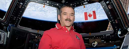 Chris Hadfield poses with the Canadian flag in the Cupola module of the International Space Station.