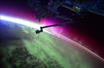 Image of an aurora and Canadarm2 from space