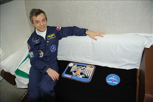 Bob Thirsk posing proudly with the emblem of his mission and the Canadian Space Agency logo