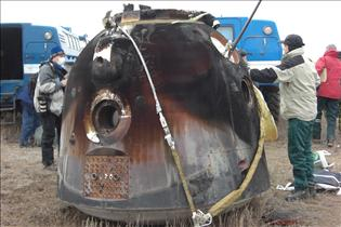 A picture of the scorched Soyuz capsule lying on the ground and about to be retrieved by a rescue team