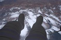 Thomas Pesquet dangling his feet in space during a spacewalk