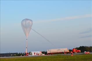 A stratospheric balloon being inflated, with the helium truck by its side