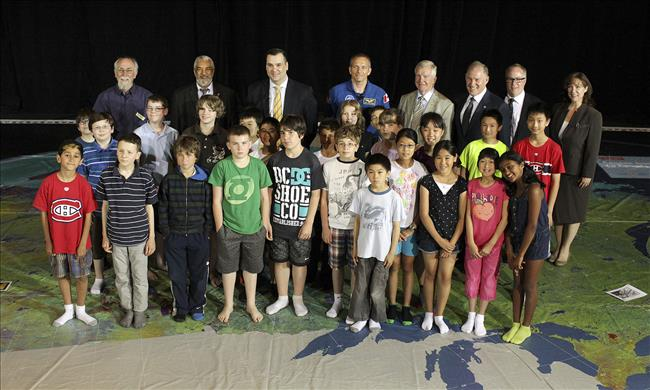 Photo de groupe incluant le ministre James Moore en compagnie de David Saint-Jacques et des enfants