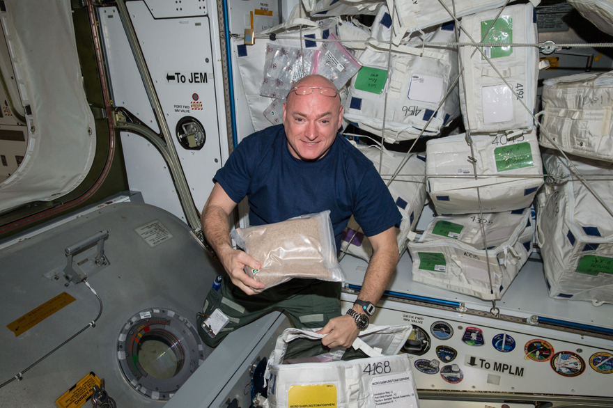 NASA Astronaut Scott Kelly poses with 600,000 tomato seeds