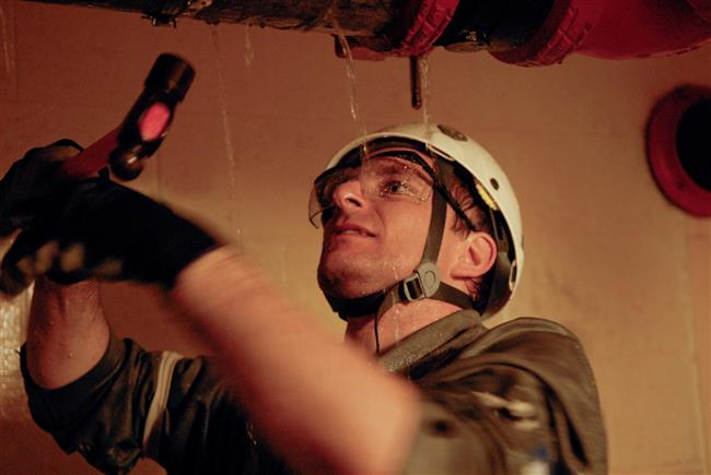 David Saint-Jacques fixing a leak during a pipe repair exercise.